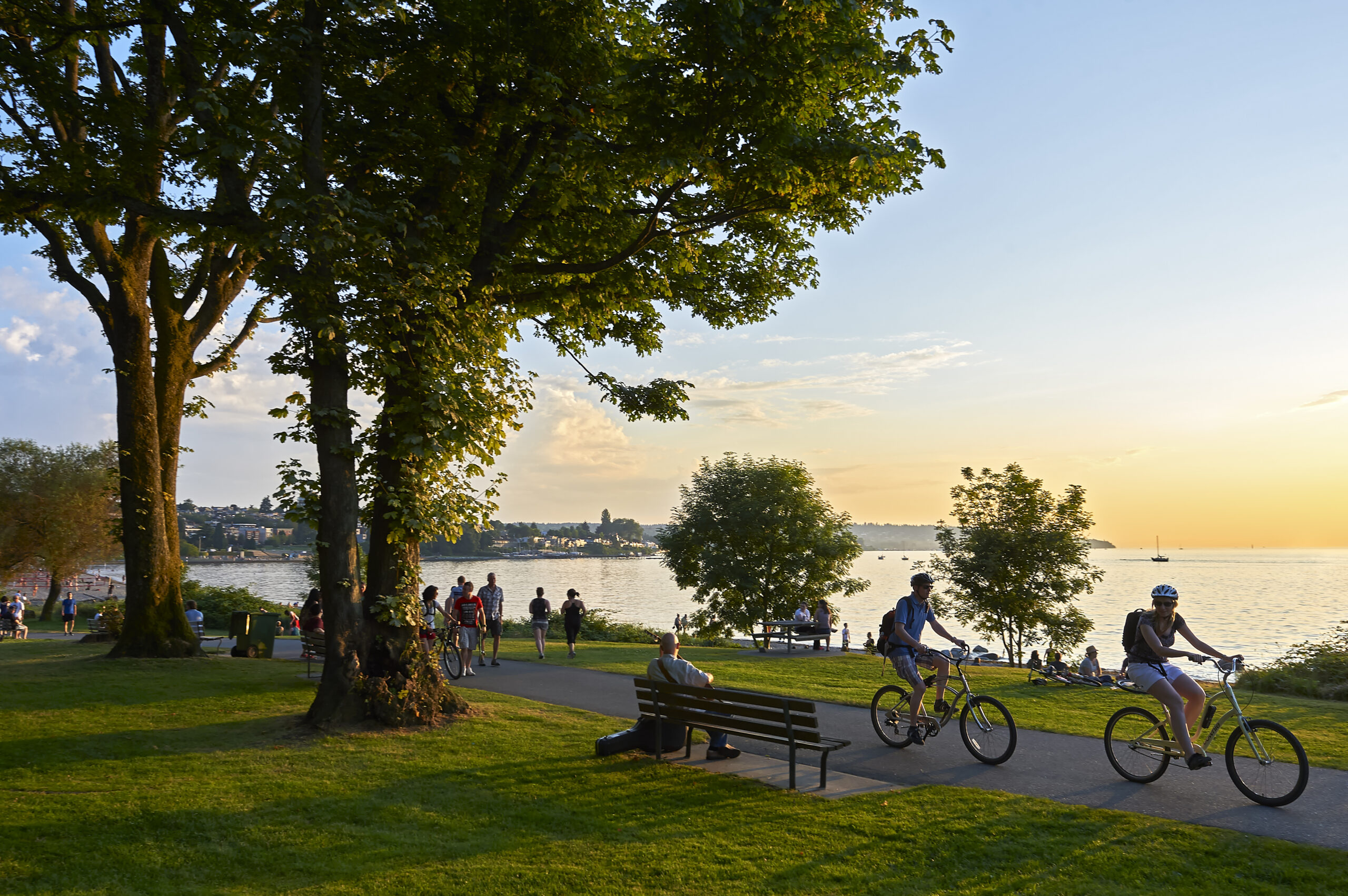 Vancouver, B.C., Canada - July 18, 2012: Young couple cycling, others walking or jogging late afternoon and enjoying the sunset at Stanley Park